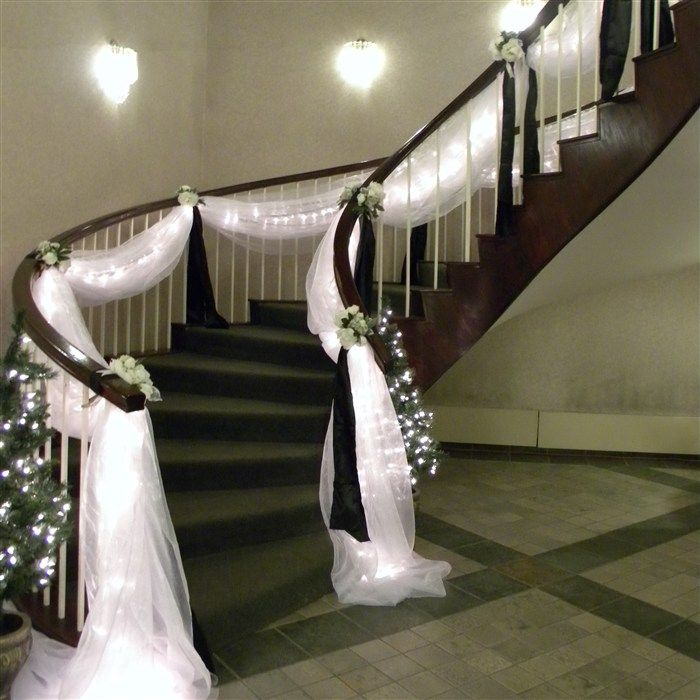 Beautiful white draping, this would be even better with red rose bouquets instead of white bouquets and some rose pedals coming down the stair case : )