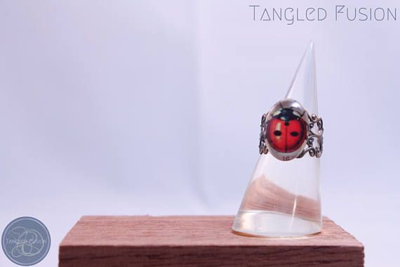 Quirky Handmade Ladybug Adjustable Ring https://www.etsy.com/au/listing/524283004/quirky-handmade-ladybug-adjustable-ring?ref=shop_home_active_3  Quirky Handmade Ladybug on Adjustable Metal Ring Base   Design: Ladybug Glass Cabochon with Old Gold Filagree Ring Base    Tangled Fusion offers a wide scope of quirky, fun jewellery and handmade creations.