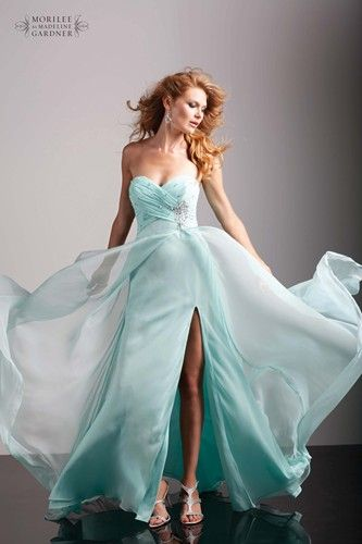 This elegant gown by Mori Lee has a high leg split, chiffon and crystal beading on the bust.