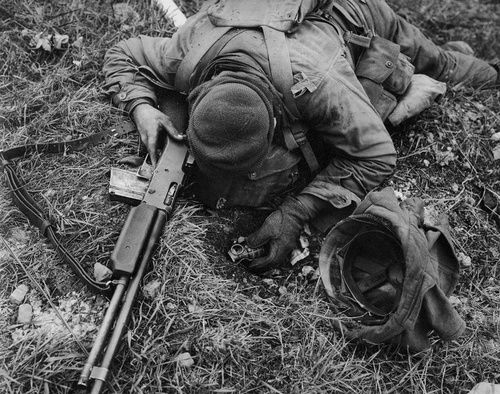 A soldier of the 87th Infantry Division, armed with his BAR and a grenade still in hand. He was killed by a German sniper inside the city of Koblenz, Germany. March 1945.