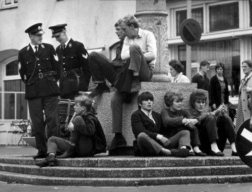 Jongeren o.a. Nozems en Pleiners zitten in het bijzijn van twee politie-agenten   op straat, -op de sokkel [van een pilaar]-, in Valkenburg (Limburg), 4 augustus   1966. [hangjongeren].