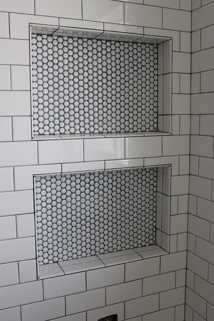 Black and white recess surrounded with subway tiles.
