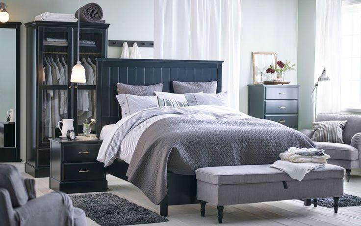 Chambre avec grand lit noir placé au centre de la pièce et textiles de lit gris. Des commodes de tailles différentes et une garde-robe à portes en verre trempé, tout en noir, complètent l'ensemble.