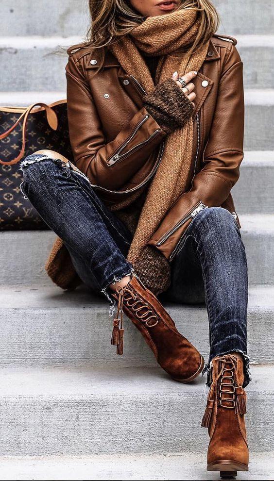 braune Leder Bikerjacke, dunkelbrauner Oversize Pullover, dunkelblaue enge Jeans mit Destroyed-Effekten, brau
