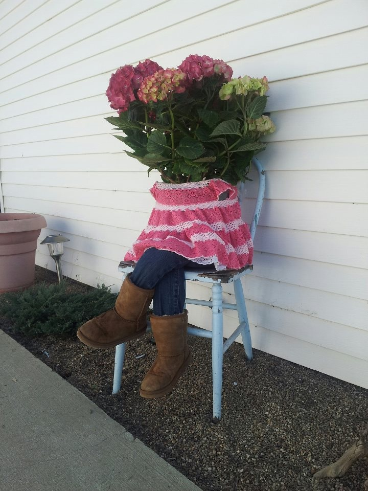 A flower planter idea. An antique chair thats weathered and some of  my daughters clothes that are too small- the jeans stuffed with empty plastic bags. Funny little girl planter!