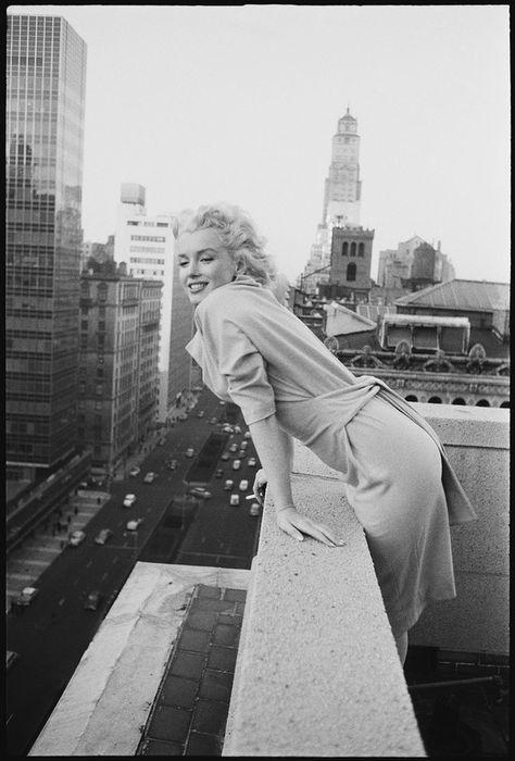 Icónicas imágenes de Marilyn asomándose a la ciudad desde el balcón de su suite en el Ambassador Hotel. | 31 Fotos cándidas de Marilyn Monroe en Nueva York