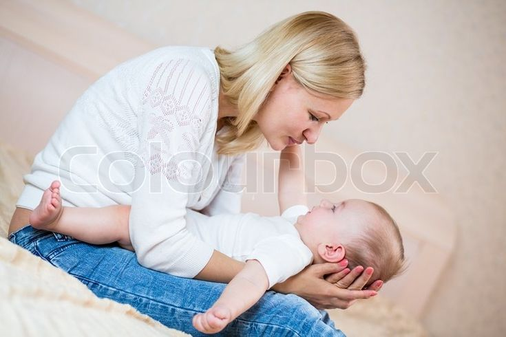 Stock image of 'Mother playing with baby boy indoors'