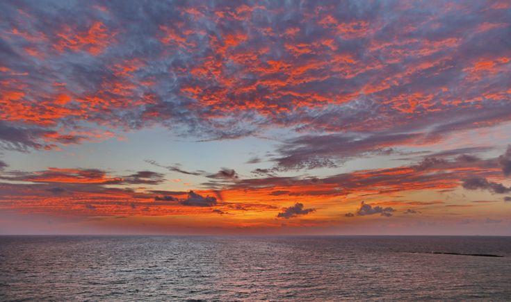 Durante le calde sere d'estate, una piña colada  e un'amaca colorata in riva al mare.