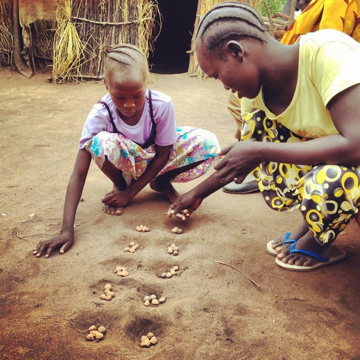 A young #refugee, who was recently reunited with her family, plays a traditional African game with her sister. © UNHCR/K. Mahoney