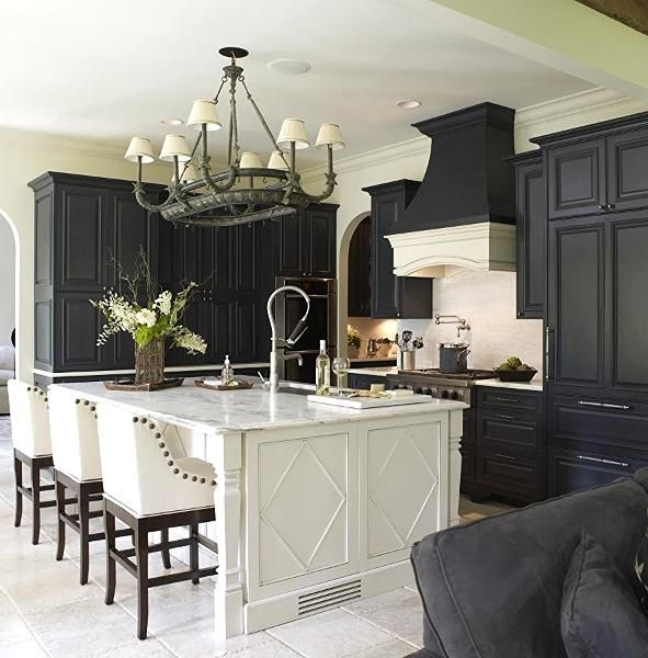 We love the combination of black cabinets with a white island in this transitional kitchen design. The designer put a lot of thought in making this kitchen completely efficient. For instance, behind the side panels of the island (to the left) is an ice-maker. This kitchen also features hidden storage, which houses a coffee station and a charging station! #design #kitchen