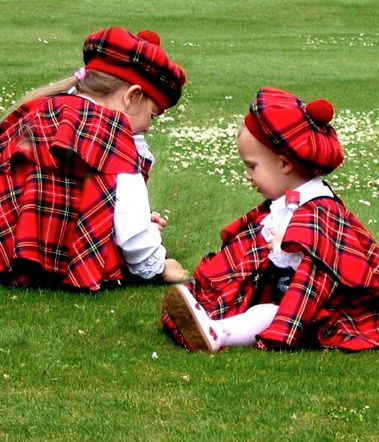 Sisters dressed in Royal Stewart Tartan making daisy chains in the springtime.
