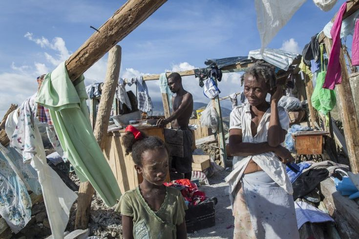 A family stands in the remains of their destroyed home in Roche-a-Bateau, southwestern Haiti, on Oct. 8, 2016. Roche-a-Bateau suffered widespread destruction with many homes destroyed as Hurricane Matthew ripped through the Caribbean devastating large parts of the island, on Oct. 4, 2016.