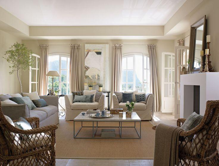 00288741. Salón en tonos claros con cojines sobre los sofás y sillones en tonos blancos y azules y dos butacas de fibras_l00288741