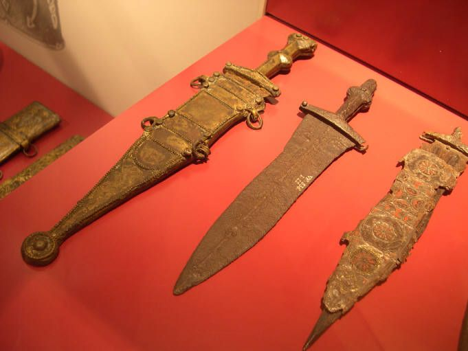 Three Roman pugios with (from left to right) the famous Leeuwen pugio with a type A sheath, type B tang, and type B blade. Next is a type A blade with a broken grip, and the last is a heavily decorated pugio with a type A sheath and type B blade.
