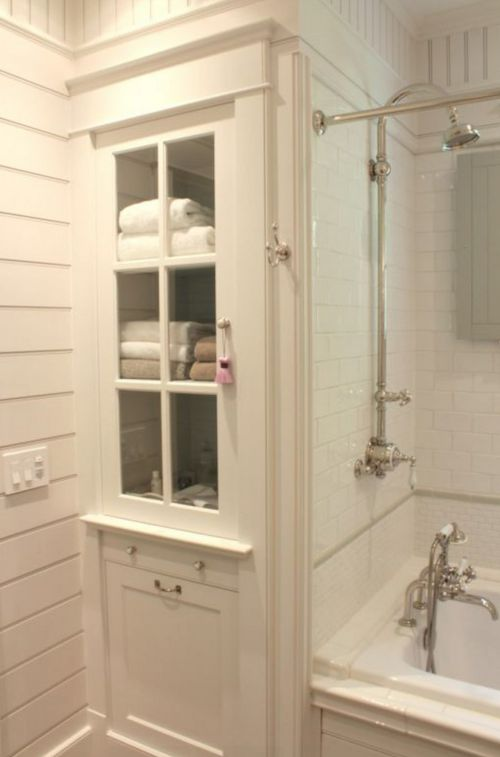 Smart bathroom storage makes use of a narrow space with great molding and a glass-front door.  Plus the exposed thermostatic shower...