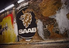 graffiti with the logo of saab in the wall.