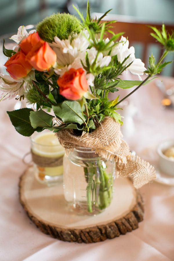 orange green and cream flowers in vase on a wooden stump