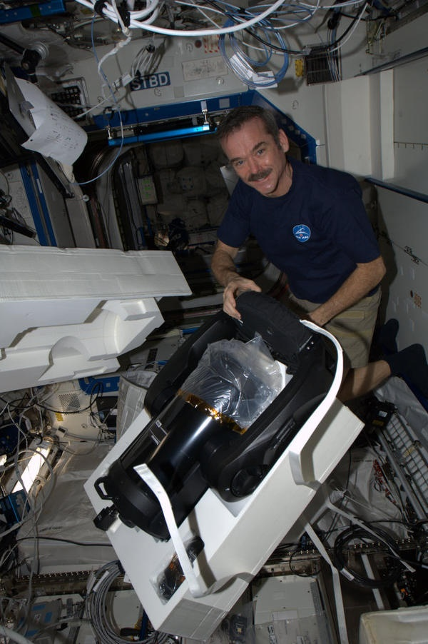 Chris Hadfield the astronaut taking the new telescope out of the box - like weightless Christmas!