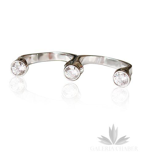 Podwójny pierścionek typu multiring, wykonany ze srebra próby 925, rodowany. W wyrobie osadzono trzy cyrkonie o szlifie diamentowym, każda o średnicy około 6 mm. Pierścionek świetnie trzyma się na dłoni, jest bardzo wygodny pomimo finezyjnego wzoru. Rozmiar regulowany istnieje możliwość dogięcia.
