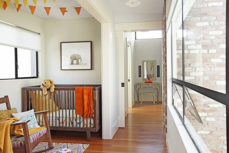 The nursery nook, a few steps from the master bedroom, is just large enough for a crib, rocking chair, and changing table (not visible). Down the short hallway, a vintage dressing table finds a place between the master bath on the left and a closet on the right. When needed, a pocket door closes off the master suite.
