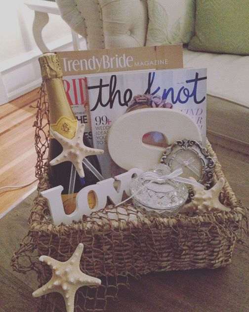 DIY Beach Wedding Engagement gift basket for the Bride-to-be! Includes: Wedding/Bridal magazines, bottle of champagne, canvas soon-to-be last name wedding initial, glass ring bowl for nightstand, picture frame ring holder, starfish, craft fishing net, tissue paper 'sand'! Contents (minus champs;) from AC Moore, glass ring bowl found at homegoods!