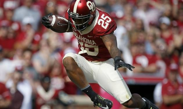 Oklahoma\'s Joe Mixon (25) leaps over Kansas State\'s Dante Barnett (22) on his way to the end zone...