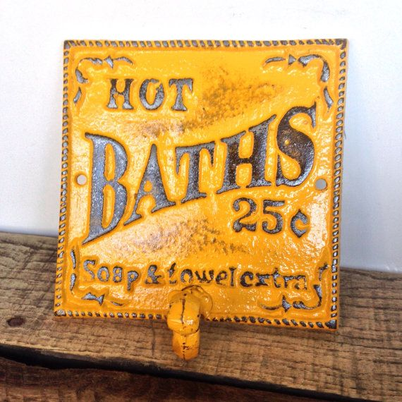 French Country/ Victorian/ Country Cottage Style solid cast iron sign with single hook. Sign reads HOT BATHS .25 CENTS, SOAP AND TOWEL EXTRA.