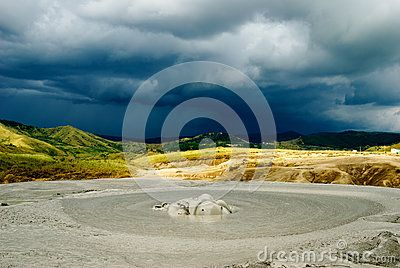 The muddy crater of a mud volcano, against a stormy sky. The geological natural reservation of Vulcanii Noroiosi is a popular tourist attraction in Romania, with its extraterrestrial appearance, caused by the ever changing mud formations and total absence of vegetation.