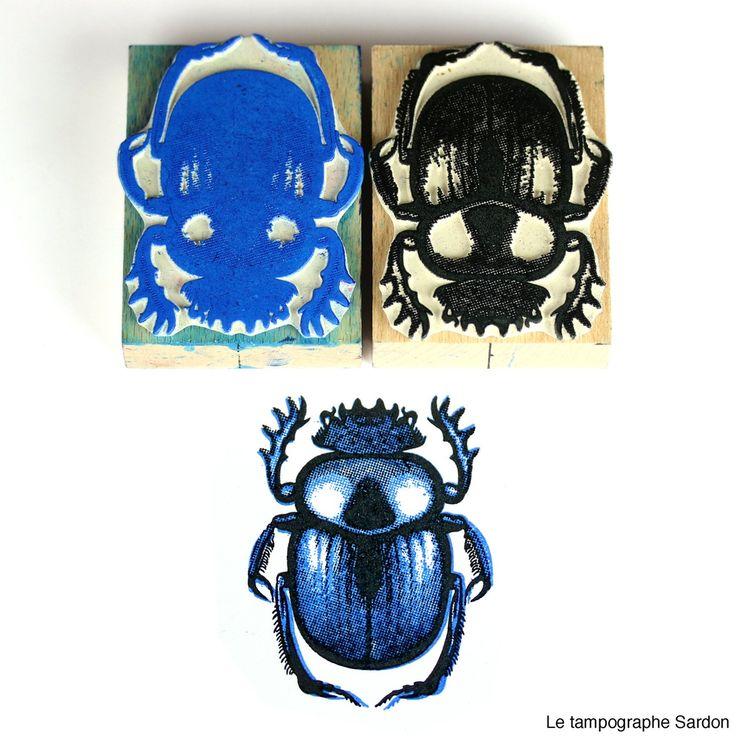 Coffret de deux tampons permettant d'imprimer une image en deux couleurs, en l'occurrence un scarabée sacré également appelé bousier. Des r...
