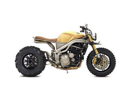 """Custom Triumph 1050 by Classified Moto -- Classified Moto describe their Custom Triumph Speed Triple 1050 as """"fast, unapologetic and beautifully ugly"""". It has a rugged aesthetic dominated by that massive eleven inch-wide ATV tyre held in place by some suspension art; a hand-built, chromoly single-sided swing arm. A custom bike that's stripped down to its raw essence, drawing on scrambler heritage with a touch of the mongrel."""