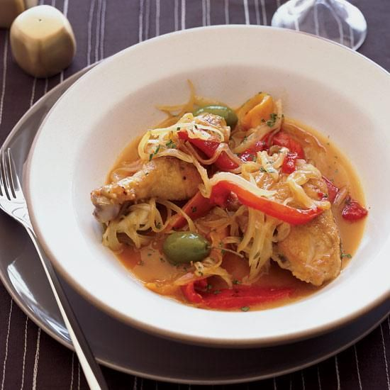 Braised Chicken with Olives and Sweet Peppers | This homey chicken dish uses low-cost but flavorful chicken thighs and is loaded with soft, sweet roasted peppers and onions. To punch up the flavor, add plump, meaty green olives, like Italian Castelvetrano or Cerignola. Serve the stew with crusty bread to sop up all of the juices.