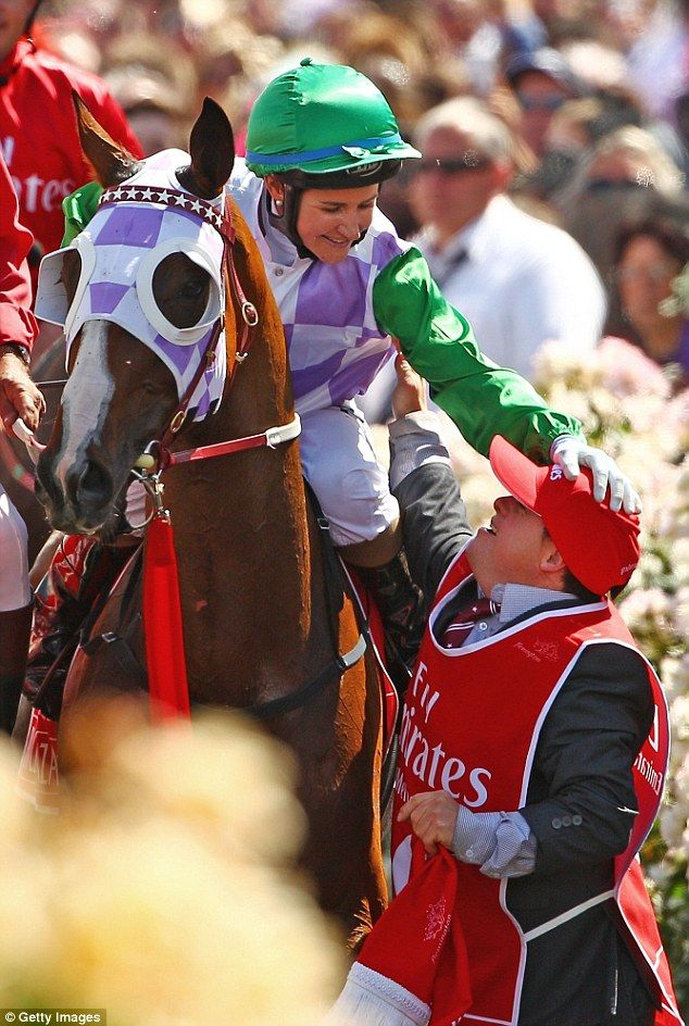 Winning Melbourne Cup jockey Michelle Payne reaches down from her mount Prince of Penzance to affectionately pat her brother Stevie.(Dailydailymail.co.uk photo)