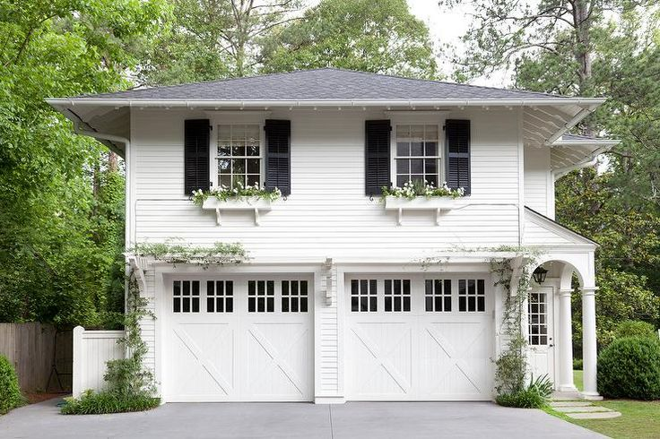Gorgeous home exterior boasts a traditional two car garage framed by white siding and positioned under an above-garage apartment with two windows flanked by black shutters and fitted with white flower boxes.