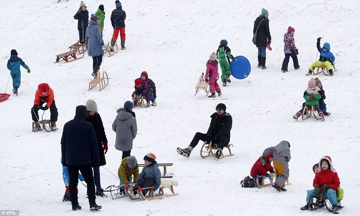 Families enjoy tobogganing in the Hasenheide park in Berlin as snow continues to fall acro...