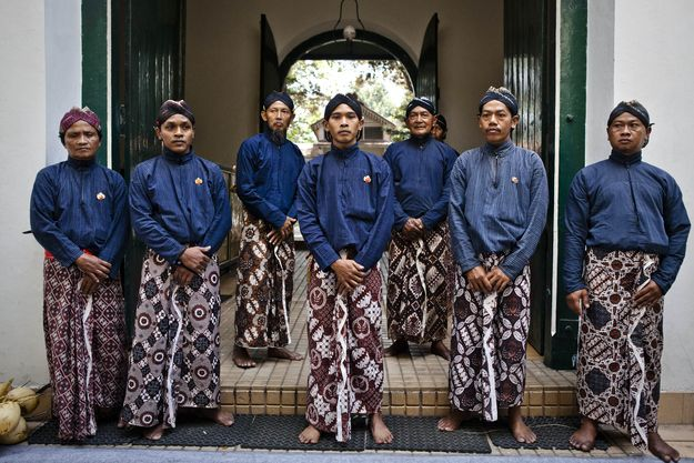 Volunteers stand outside Kraton Palace during royal Indonesian wedding 10/13