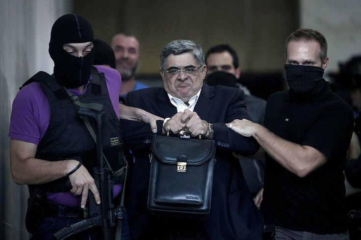 The leader of ultra-right wing Golden Dawn party Nikos Michaloliakos is escorted by masked police officers to the prosecutor from the police headquarters in Athens on September 28, 2013. AFP PHOTO / Angelos Tzortzinis