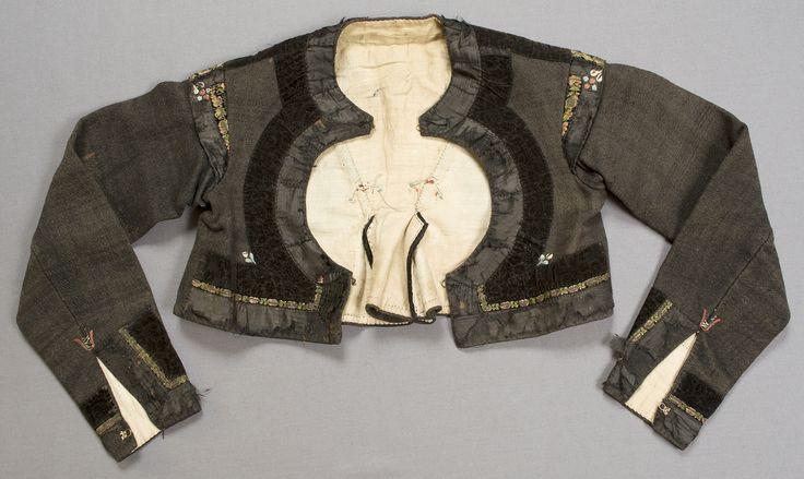 Svart (brunsvart) vadmalströja garnerad med band och broderier. Tröjan har rund öppning fram på bröstet, skört bak och isydda kilar samt axelkarm på ärmen.