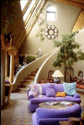 Extravagant natural home underpinned by a boho vibe. Lovely curved staircase, lilac couches, organic concrete walls and rustic timber skylight windows.