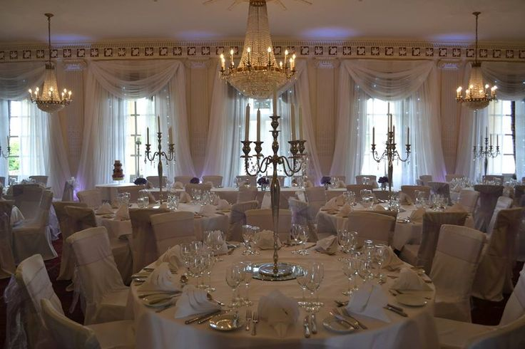 buxted park hotel ballroom wedding reception - voile curtain draping with uplighters and candelabra centrepieces from pollen4hire