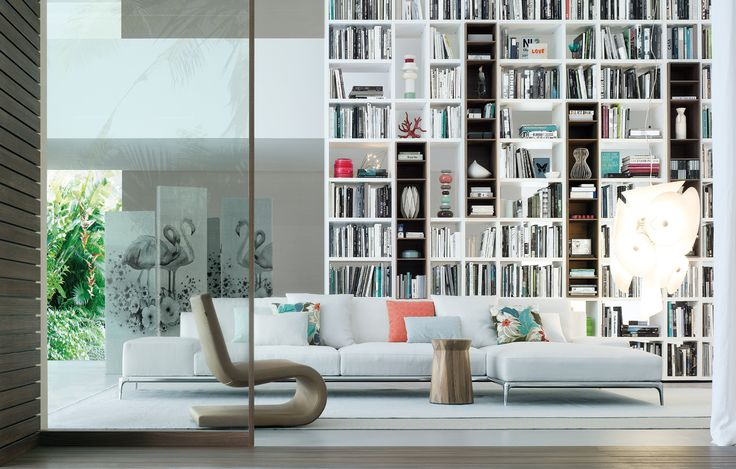 Beautiful floor to ceiling bookshelves with a gorgeous large-scale sofa (Park from Poliform), accented with pops of coral, turquoise and warm brown.