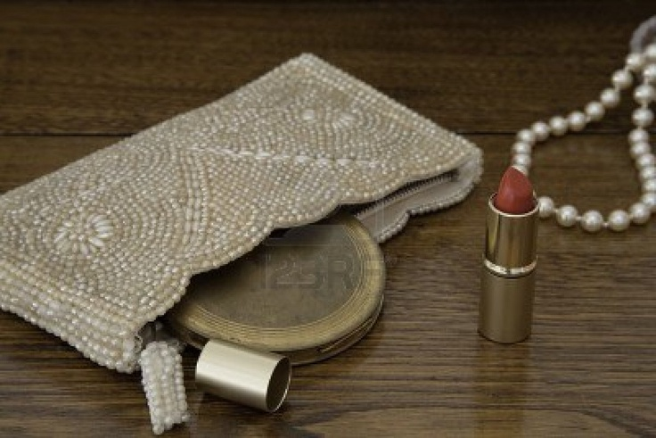 ヴィンテージパウダーコンパクト、オープン、明るい赤の口紅のチューブとダークアンティークオークのドレッシングテーブルの上に真珠の文字列で1920パールハンドバッグ ストックフォト