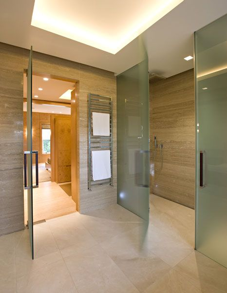bathroom walls in travertine classico and floor and shower tray crema marfil marble honed