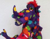 Puff is of course a Magic Dragon, he is a great listener, and looks fantastic as well. He will look over you with his magic. He has pointy teeth and a separate tongue. Stands about 25cm high. made from colourful cotton and wears a beaded necklace. Something to be loved by ages over 6. [There are wire supports in his arms] One of a kind.  SOLD