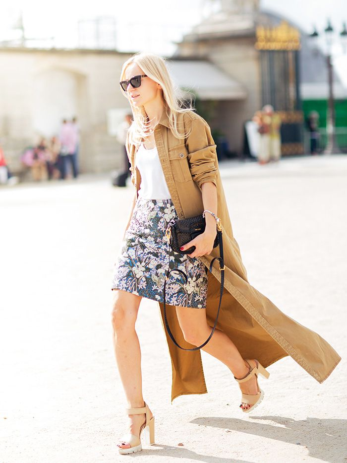 A white top is worn with a fitted floral pencil skirt, nude platform heels, sunglasses, a long tan button-up, and a black crossbody bag.