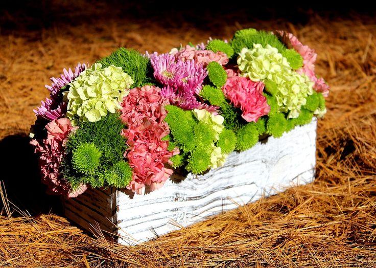 Crisantemos entre claveles y hortensias en caja rústica.