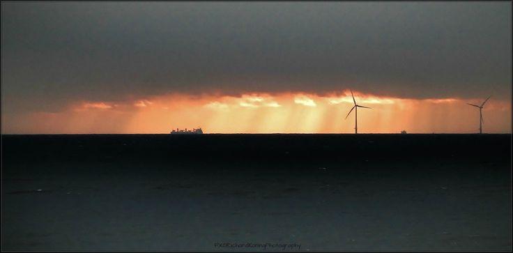 Donkere wolken boven de zee.....aan de horizon de ondergaande zon.