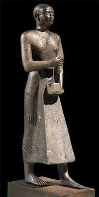 Estatua en bronce de KHONSIRDIS. Sumo Sarcedote divino durante el reinado del faraón Psamético I (610 al 526 a.C.) fundador de la Dinastía XXVI  en los inicios del Período Tardío de Egipto. Representado con la cabeza rapada y ataviado con un manto de piel de leopardo. Museo Británico de Londres.