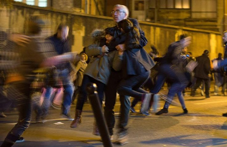 A man carries two children as panic broke out among mourners who payed their respect at the terroristic attacks sites at restaurant Le Petit Cambodge and the Carillon Hotel in Paris. Nov. 15, 2015.