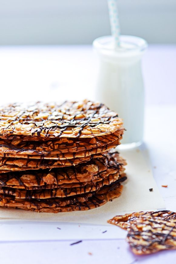 """Florentine Cookies with Chocolate Drizzles (Sweetapolita). """"Decadent nutty, buttery, caramelized cookie discs drizzled in dark chocolate. Recipe as printed in The Cookiepedia cookbook by Stacy Adimando."""""""
