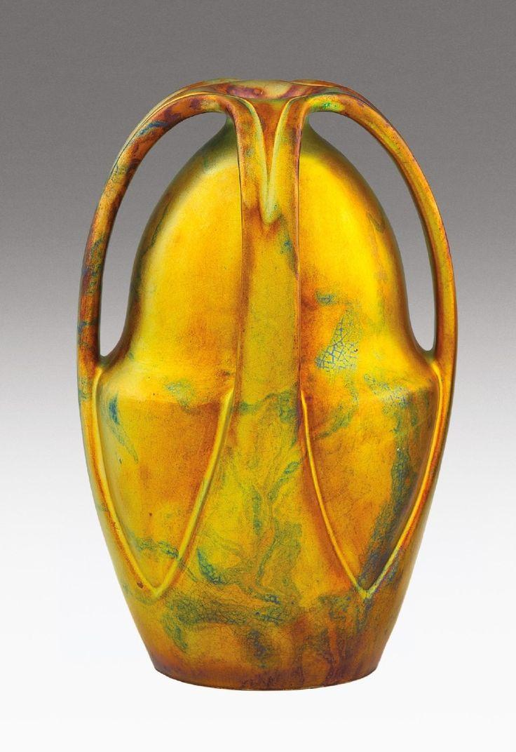 Zsolnay szecessziós négyfülű váza   Korongozott és kézzel alakított fehércserép. Savmaratott felületén, selymesfényű, márványozott, többrétegű, színes eozimázakkal festett.   Formaterv: Apáti Abt Sándor, 1900.  Kiállítva: az 1902.-es Torinói Nemzetközi Művészeti Kiállításon.   Alján jelzett: masszába nyomott 6198 (formaszám)   és M., valamint alappal megegyező, kerek, domborodó, pecsétszerű márkajelzés.  Zsolnay, Pécs, 1900. BA17/k800e